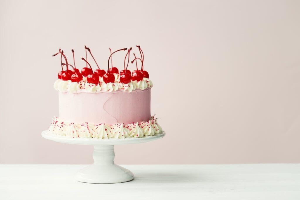 gräddtårta, tårta med grädda, spritsa grädde, cocktailbär på tårta